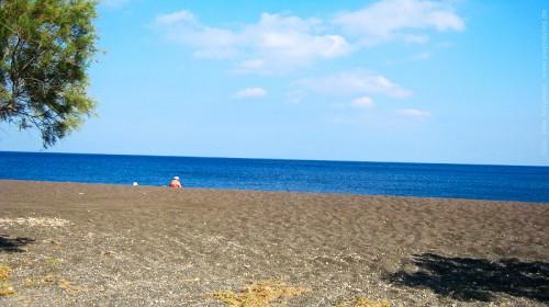 Schwarzer Strand mit einem Strandbesucher