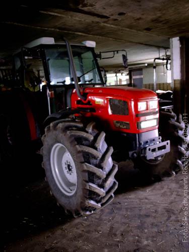 Roter Traktor im Stall