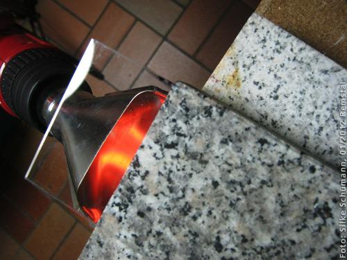 Heißluft-Pistole gegen Acrylglas auf einer Granitplatte gehalten
